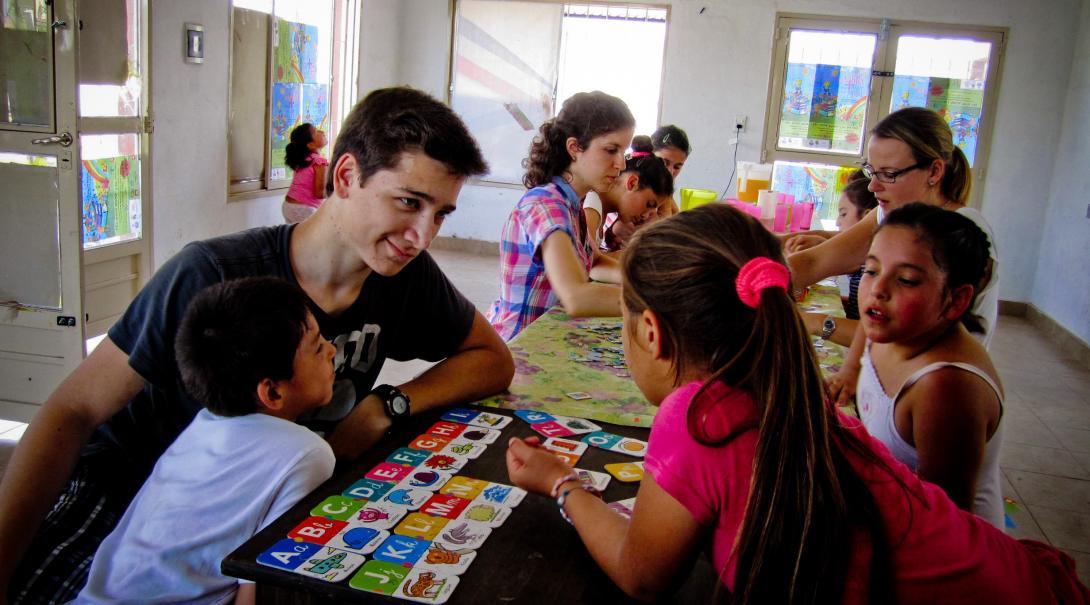 Ayudar a los niños a aprender jugando y realizar actividades y juegos didácticos Joven voluntario en Argentina enseñándole inglés básico a los niños.
